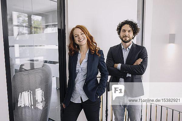 Porträt eines selbstbewussten Geschäftsmannes und einer selbstbewussten Geschäftsfrau im Amt