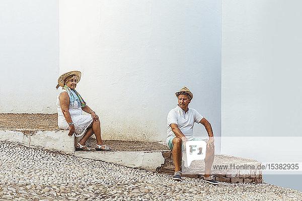Älteres Touristenpaar,  das auf Stufen in einem Dorf sitzt,  El Roc de Sant Gaieta,  Spanien
