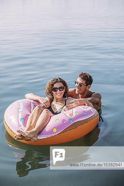 Glückliches junges Paar badet im Meer auf einem aufblasbaren Schwimmer in Donutform