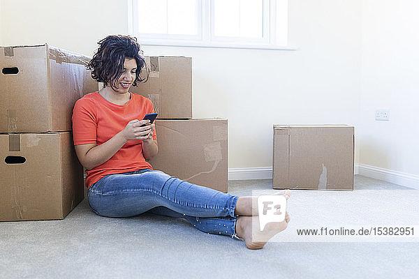 Frau sitzt in neuer Wohnung auf dem Boden und benutzt Mobiltelefon
