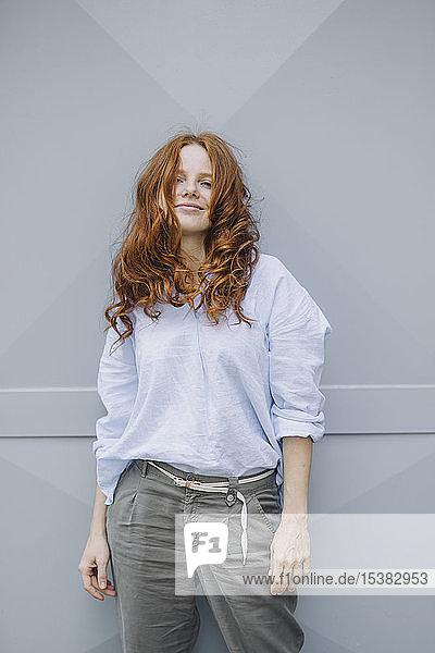 Porträt einer schönen rothaarigen Frau  die an einer Wand steht