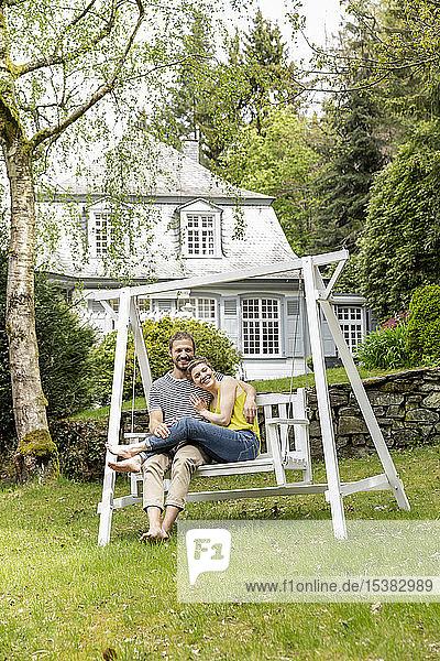 Glückliches Paar entspannt sich im Garten seines Hauses