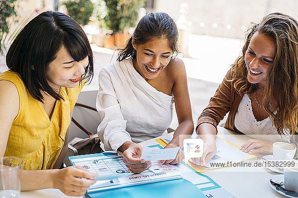 Glückliche multikulturelle Studentinnen treffen sich in einem Cafe und organisieren ihren Stundenplan