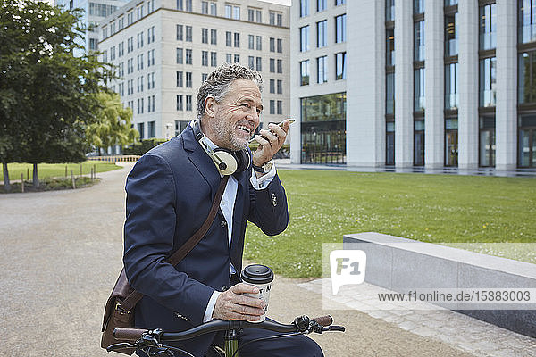 Mature businessman with bicycle using smartphone in the city