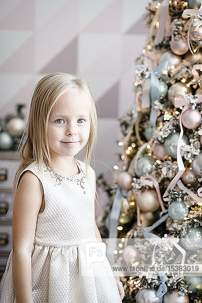 Portrait of smiling little girl standing in front of lighted Christmas tree