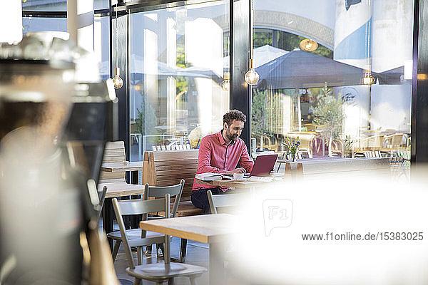 Junger Mann benutzt Laptop in einem Café
