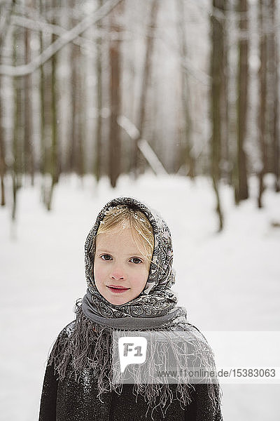 Portrait of little girl wearing headscarf standing in front of winter forest