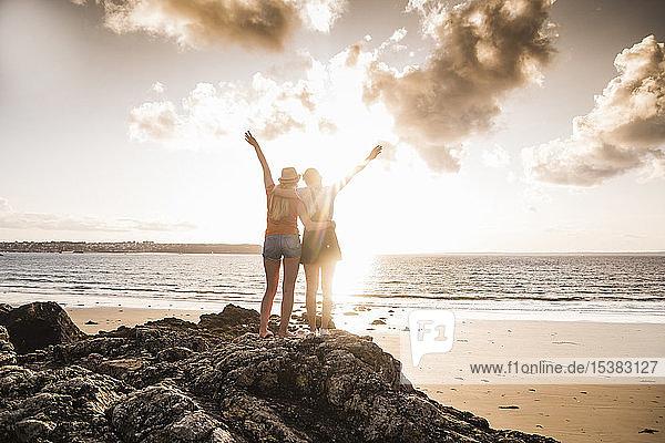 Zwei Freundinnen stehen am felsigen Strand  winken bei Sonnenuntergang  Rückansicht