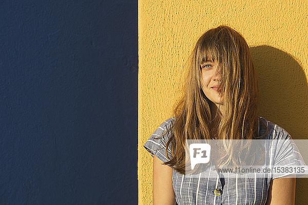 Porträt einer Frau vor gelben und blauen Wänden