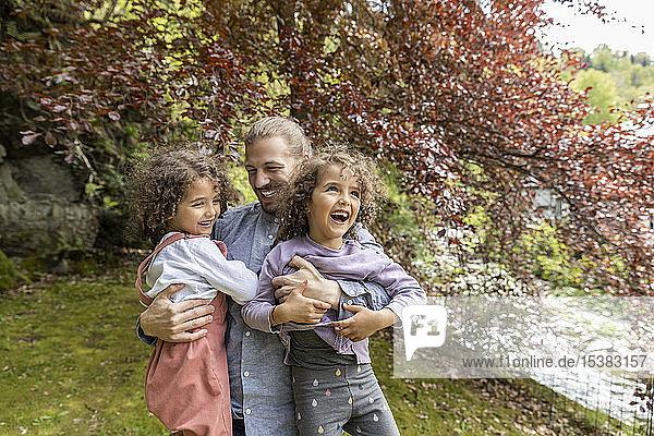 Glücklicher Vater amüsiert sich mit zwei Jungen im Garten