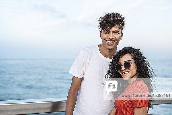 Porträt eines glücklichen jungen Paares am Meer