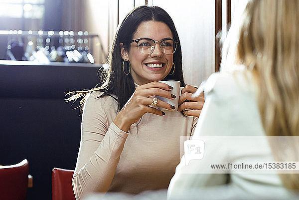 Porträt einer lächelnden Frau mit Freundin in einem Cafe