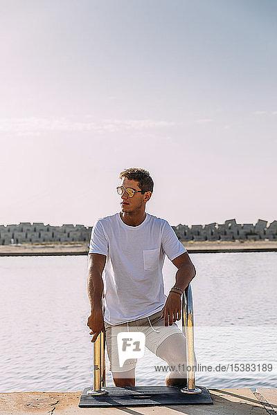 Junger Mann auf einem Steg im Schwimmbereich