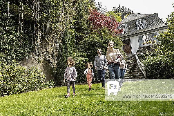 Glückliche Großfamilie beim Spaziergang im Garten ihres Hauses
