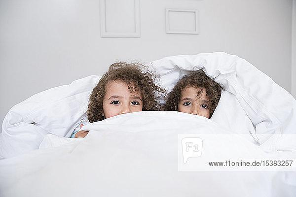 Porträt von zwei süßen Zwillingsbrüdern im Bett