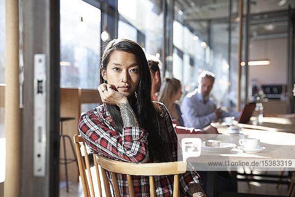 Porträt einer Frau mit Kollegen in einem Cafe