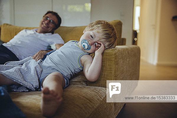 Kleiner Junge mit Schnuller  auf dem Sofa liegend  schlafend