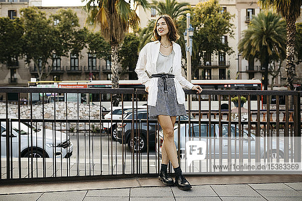 Smiling woman leaning on a city fence with a lot of traffic on the streets