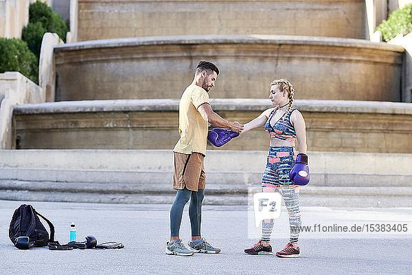Fitnesstrainer übt Boxunterricht mit einer jungen Frau im Freien in der Stadt  die einen Boxhandschuh anzieht