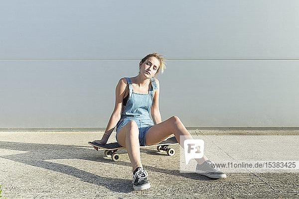 Coole junge Frau sitzt auf einem Skateboard