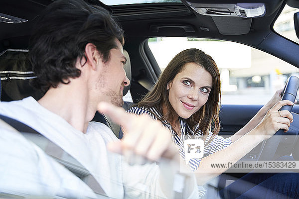 Happy couple in a car with woman driving and man pointing his finger