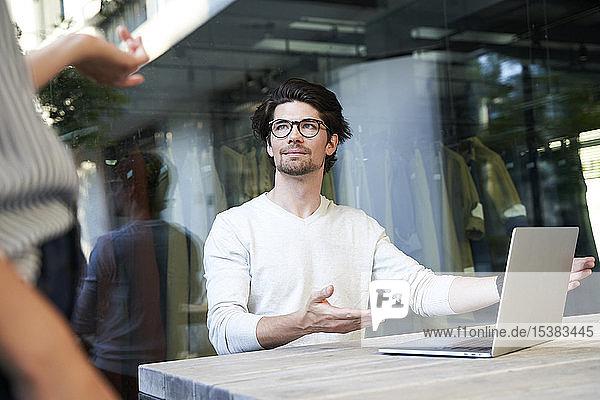 Geschäftsmann mit Laptop trifft Kollege in der Stadt