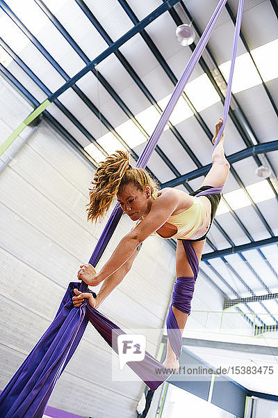 Young woman doing aerial silk in an exercise room