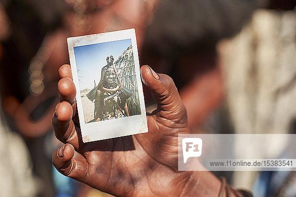 Frau vom Mudimba-Stamm mit einem Bild von sich selbst  Onocua  Angola.