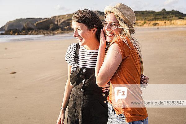 Zwei Freundinnen amüsieren sich  gehen am Strand spazieren