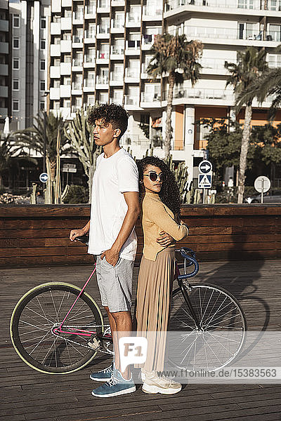 Cool couple with bicycle in the city  standing back to back