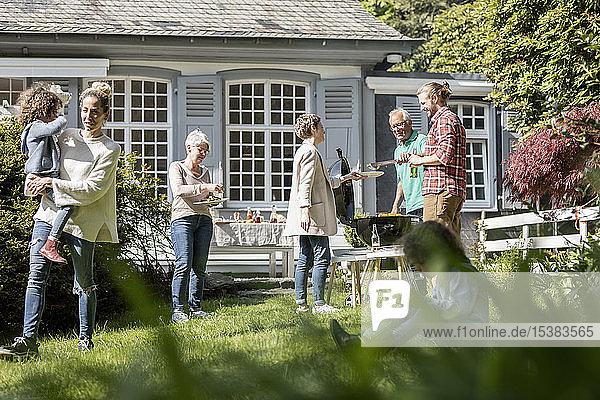 Großfamilie beim Grillen im Garten