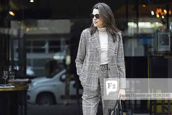 Stilvolle Frau steht vor einem Restaurant und sieht sich um