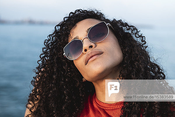 Beautiful woman  wearing sunglasses  standing at the sea