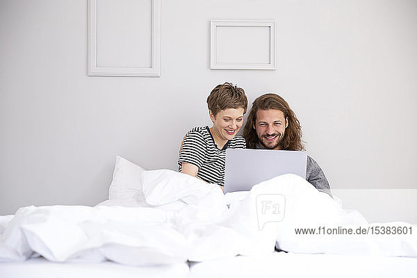 Young couple with laptop in bed at home