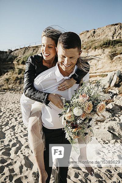 Glücklicher Bräutigam trägt Braut huckepack am Strand