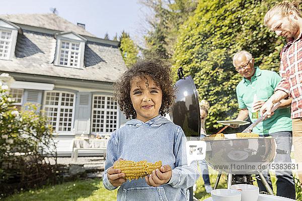 Porträt eines Jungen mit Maiskolben auf einem Familiengrill im Garten