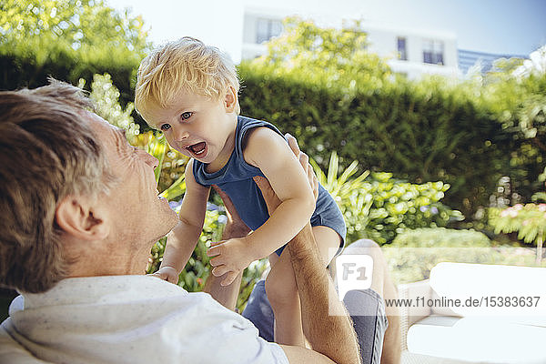 Father sitting in garden,  playing with his little son