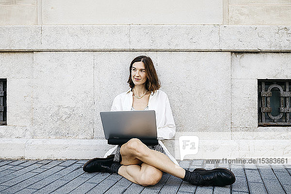 Businesswoman sitting on ground in the city  using laptop