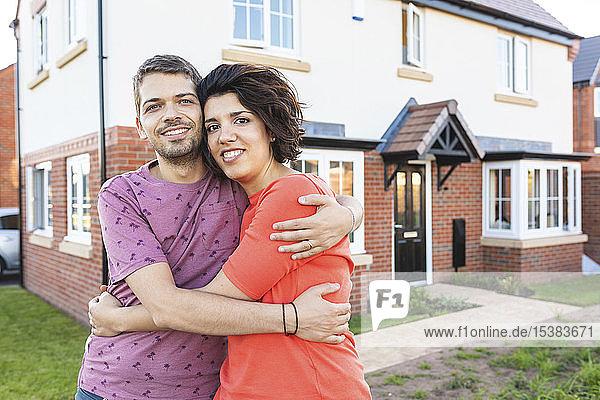 Porträt eines glücklichen Paares  das sich vor seinem neuen Zuhause umarmt