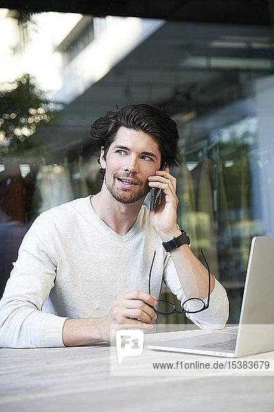 Gelegenheits-Geschäftsmann mit Laptop und Handy in der Stadt