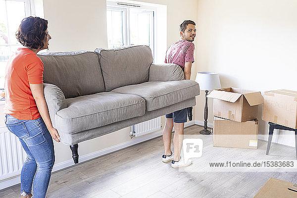 Ehepaar zieht mit einem Sofa in ein neues Heim ein