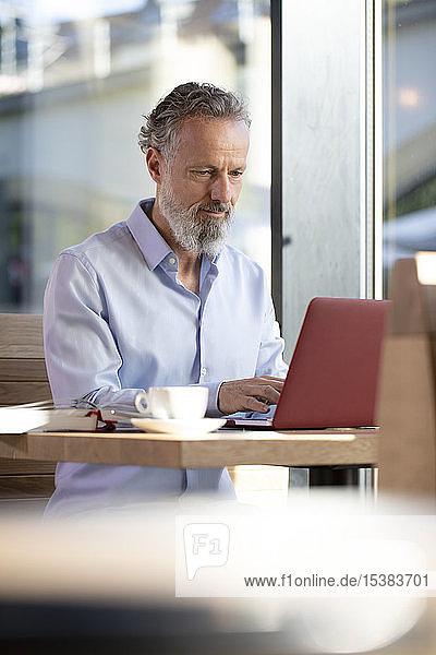 Erwachsener Mann benutzt Laptop in einem Café