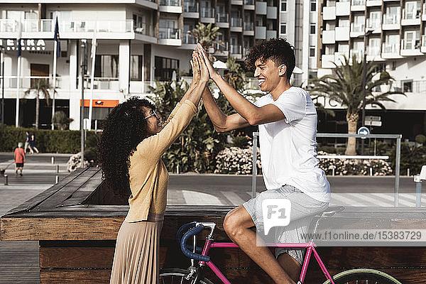 Junges Paar mit Fahrrad  High-Five in der Stadt Junges Paar mit Fahrrad, High-Five in der Stadt
