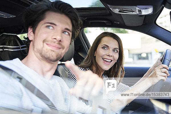Glückliches Paar in einem Auto mit Frau am Steuer und Mann  der mit dem Finger zeigt