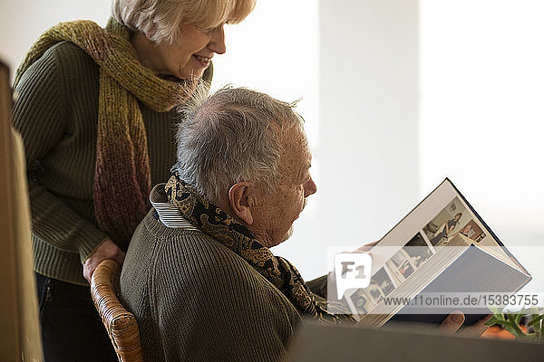 Senior couple looking at photo album surrounded by cardboard boxes in an empty room