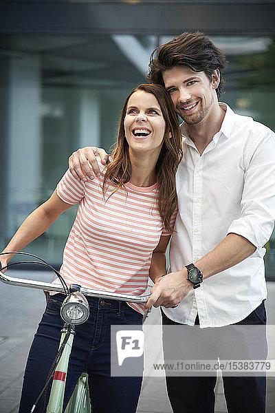 Glückliches Paar mit Fahrrad in der Stadt