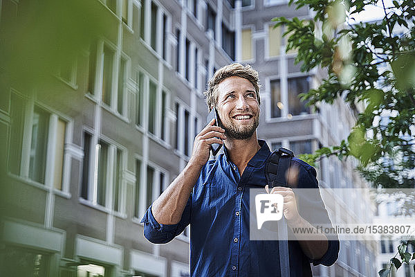 Smiling young businessman on the phone in the city