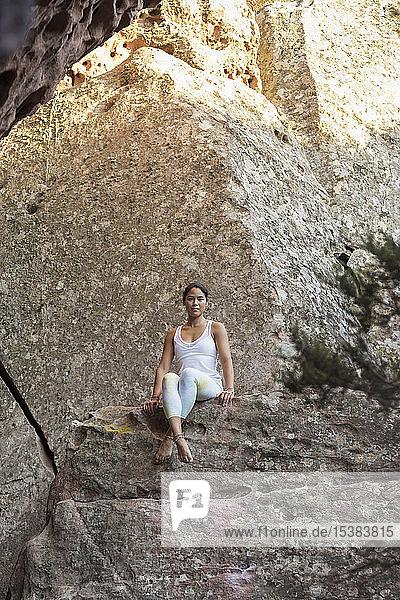 Junge Asiatin sitzt auf einem Felsen
