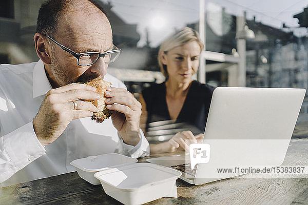 Geschäftsmann isst Hamburger im Café  während ein Kollege seinen Laptop benutzt