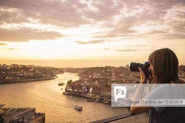 Frau beim Fotografieren von Porto bei Sonnenuntergang,  Portugal